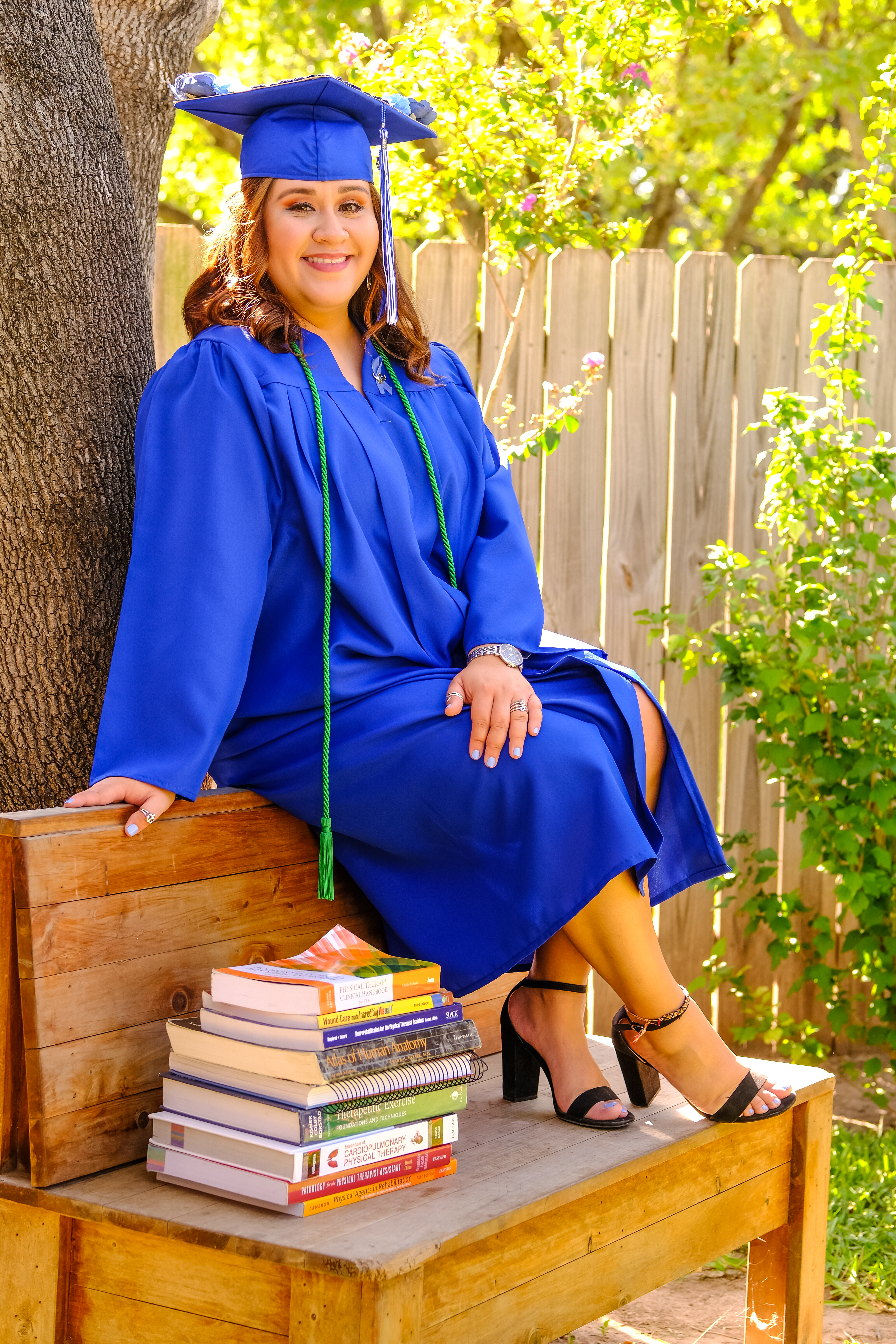 female college grad sitting on wood bench with textbooks in regalia